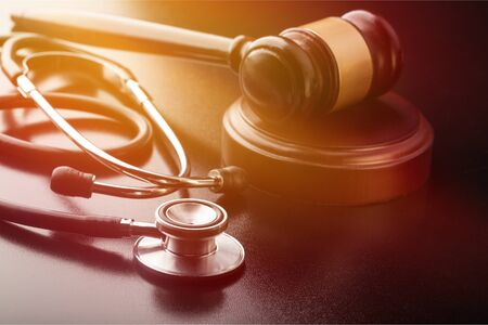 Wooden gavel and stethoscope close-up view