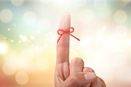 Rope bow on finger pointing on light background