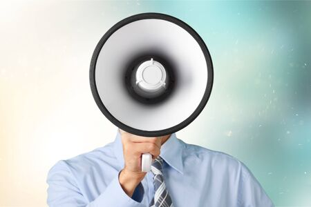Young businessman talking on the megaphone on white background Stockfoto