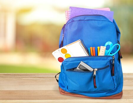 Bunte Schulsachen im Rucksack auf Holzuntergrund