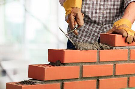 Bricklayer worker installing brick masonry on exterior