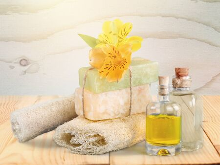 Healthy spa concept with handmade soap bars, oil bottles, sponge and flowers