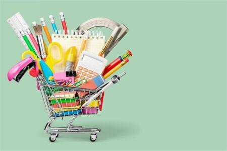 Útiles escolares coloridos en carrito de compras