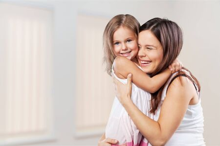 Moeder en dochter knuffelen in lichte slaapkamer