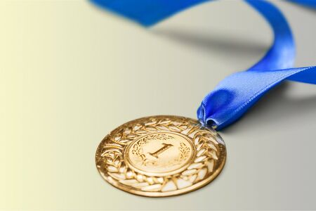 Gold medal with ribbon on background