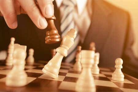 Business man playing chess - checkmate. Close-up chess pieces 免版税图像