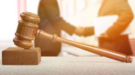 Wooden judge hammer, handshake of business people on background Stock Photo