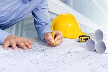 Architect bezig met bouw blauwdruk. Architecten werkplek - architectonisch project, blauwdrukken, helm, meetlint, bouwconcept. Technische hulpmiddelen.