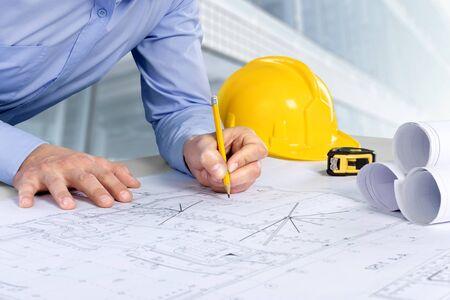 Architekt, der an Bauplan arbeitet. Architektenarbeitsplatz - Architekturprojekt, Blaupausen, Helm, Maßband, Baukonzept. Engineering-Tools.