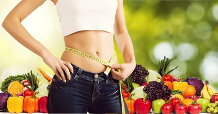Young woman with measuring tape on healthy food background