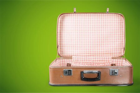 Empty Vintage Suitcase open isolated on green background