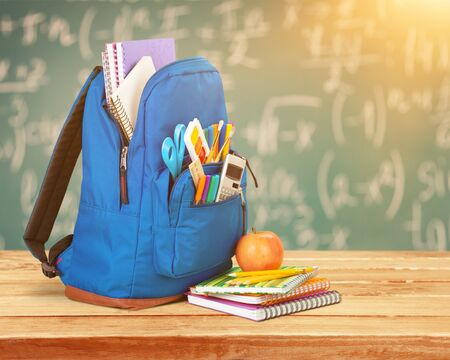 Open blue school backpack and notebook with apple Stock Photo