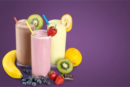 Fruit Smoothies with Straws Isolated on a purple background