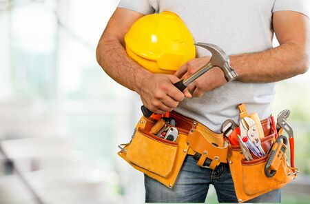 Bricklayer hands holding hardhat and tools