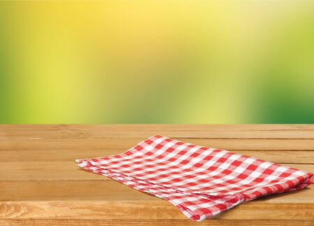 Wooden table and colorful napkin on background