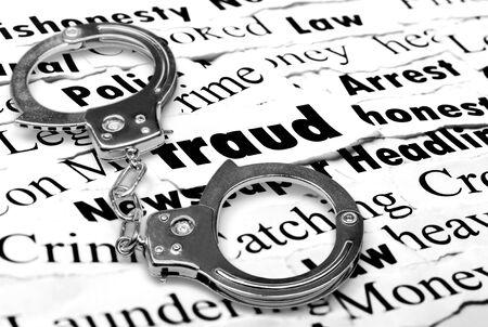 Handcuffs frame the word fraud among newspaper
