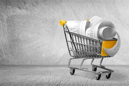 Shopping cart full with bills on background