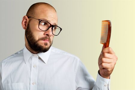 Hombre con gafas negras sosteniendo el peine en la pared blanca