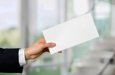 Hand of business man in suit holding white card
