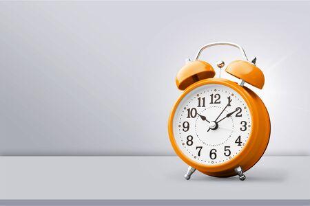 Orange retro alarm clock on wooden table on wall background