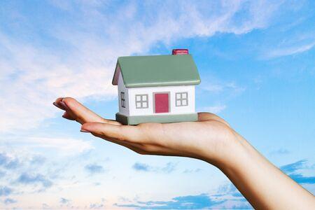 Concept de construction, d'hypothèque, d'immobilier et de propriété - gros plan du modèle de maison tenant la main