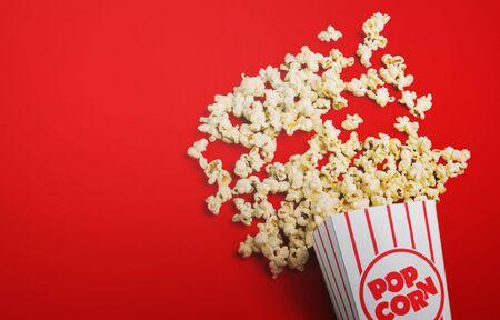 Popcorn versato su uno sfondo rosso, cinema, film e concetto di intrattenimento