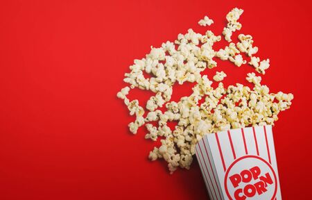 Spilled popcorn on a red background, cinema, movies and entertainment concept Archivio Fotografico