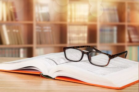 Close-up Black reading glasses and book on blurred library background
