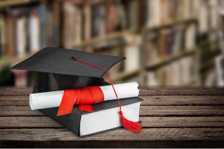 Graduation mortarboard on book on background Stock fotó