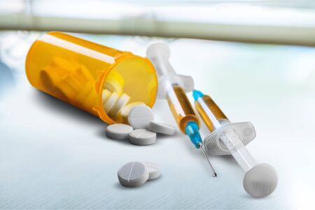 Opioid epidemic, drug abuse concept with closeup on two heroin syringes or other narcotics surrounded by scattered prescription opioids. Oxycodone is the generic name for a range of opioid painkillers