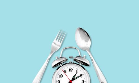 Alarm clock. Fork and knife instead of clock hands. Concept of intermittent fasting, lunchtime, diet and weight loss          - Image