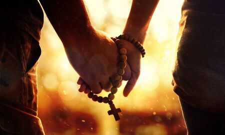Couple praying together. Holding rosary in hand. Stock Photo