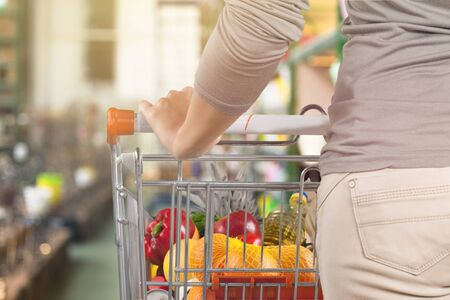 Woman with cart shopping and holding buttle