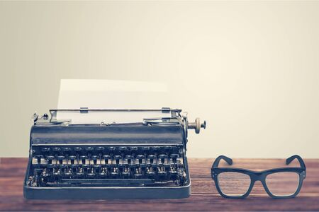 Retro black typewriter and spectacles on wooden background