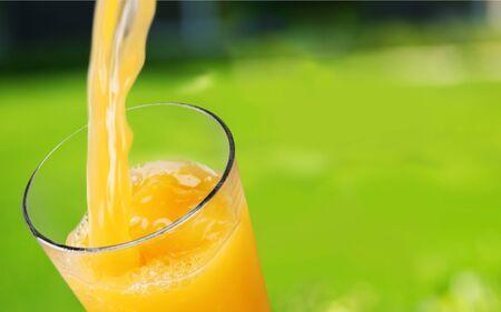 Orange juice glass on green blurred garden Background