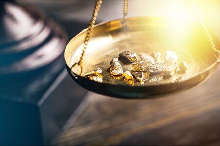 Kleine goudklompjes in een antieke maat Stockfoto