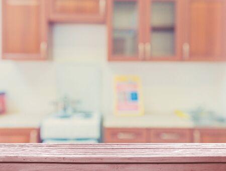 Piano del tavolo in legno sulla cucina sfocata Archivio Fotografico
