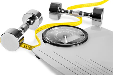 Healthy lifestyle fitness weight control concept. Closeup  dumbbells with measuring tape on  scales