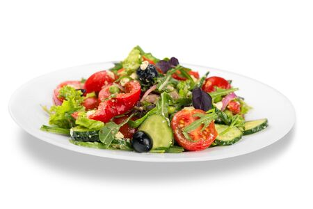 Close-up photo of fresh salad with vegetables in white plate