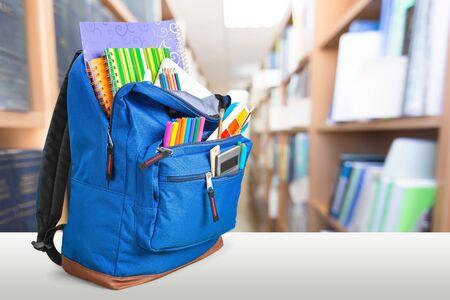 Schulrucksack mit Briefpapier auf Holztisch Standard-Bild