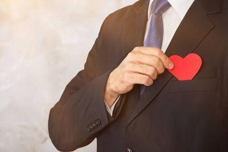 Homme d'affaires avec coeur rouge sur la poitrine gauche isolé sur fond blanc avec un tracé de détourage.