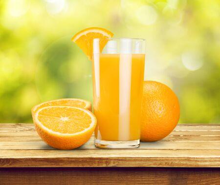 Sinaasappelsap en schijfjes sinaasappel op achtergrond Stockfoto