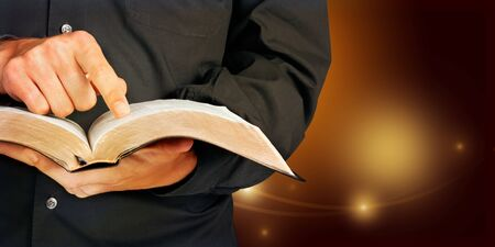 Closeup on a Priest Holding a Bible and Pointing Finger