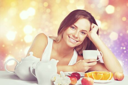 Attracive young woman enjoying tea and fruits on breakfast