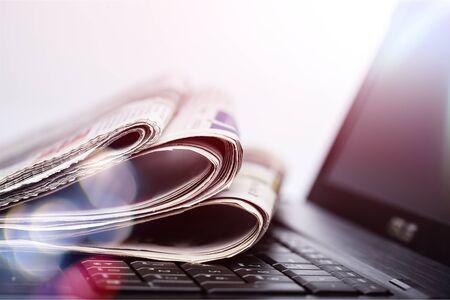 Periódicos en la computadora portátil. Noticias en línea. Aislado Foto de archivo