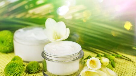 Cosmetic cream with white flowers on table