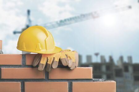 Yellow helmet with equipment on construction background Stock Photo
