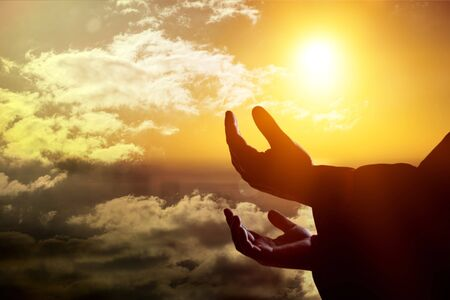 Male hands with open palm praying to god over sunrise background          - Image Stock Photo