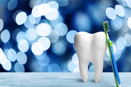 Big tooth model and toothbrush on light background Stock Photo