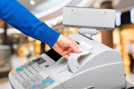 Caisse enregistreuse avec écran LCD et main des travailleurs tenant le papier de réception sur l'intérieur du supermarché floue